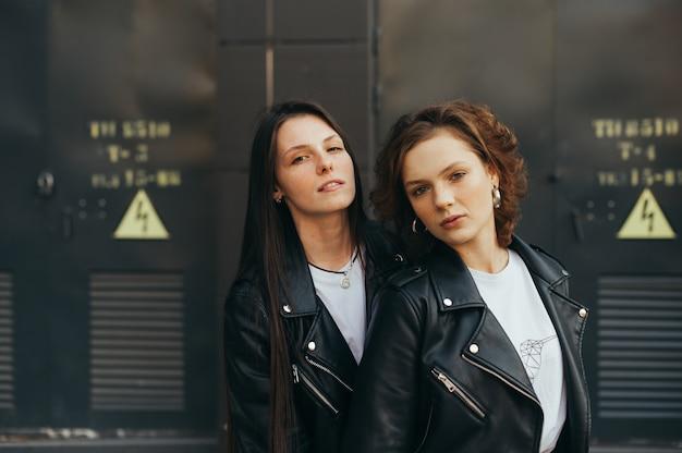 Due modelli su sfondo nero, indossano giacche di pelle
