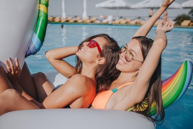 Due modelli agghiaccianti sul galleggiante in piscina. indossano costumi da bagno e occhiali da sole. primo modello freddo e tieni gli occhi chiusi. il secondo allunga le braccia e sorride. sono rilassati e sexy.