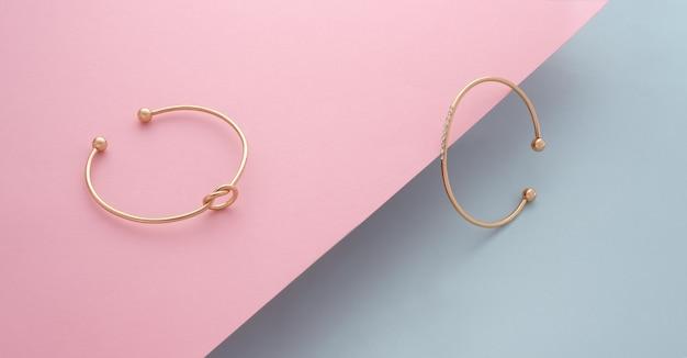 Due braccialetti moderni su carta rosa diagonale inclinata su sfondo blu