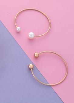 Due braccialetti moderni con perle su sfondo di carta rosa e viola con spazio per le copie