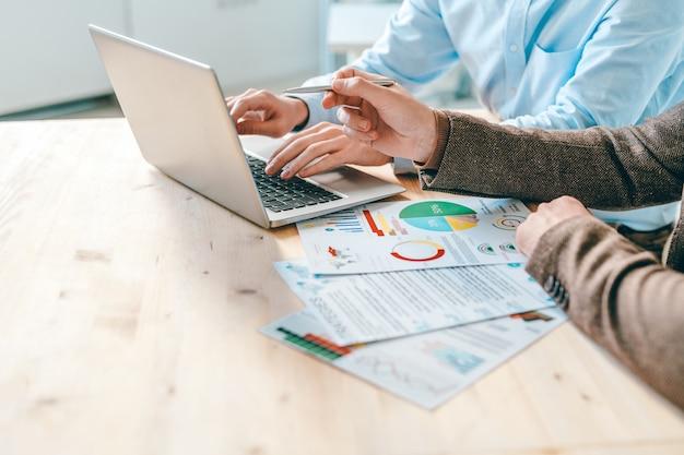Due moderni analisti aziendali discutono idee per la presentazione sul display del laptop e indicano le informazioni