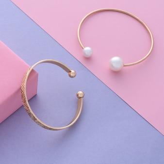 Due bracciali in oro moderno con perle e classici su sfondo diagonale in colori pastello