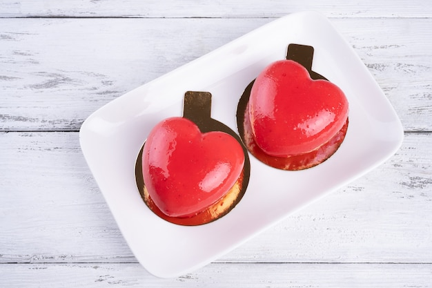 Due torte di mousse sotto forma di cuore rosso su un piatto bianco su fondo di legno bianco