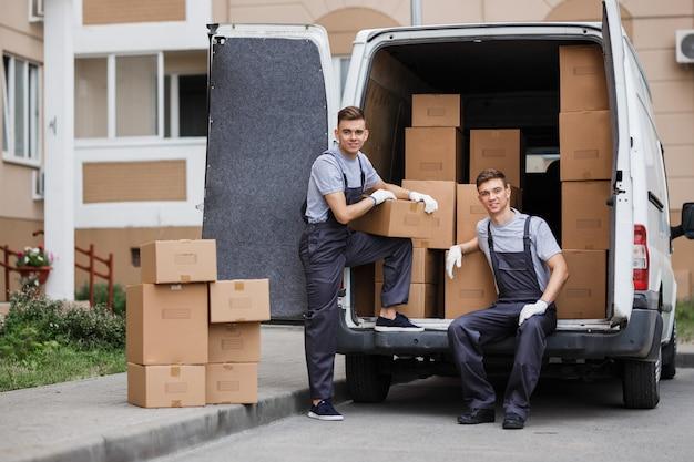 Due traslochi in divisa stanno scaricando il furgone pieno di scatole servizio trasloco casa