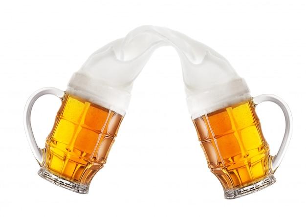 Due tazze di birra con schiuma che si versano l'una nell'altra