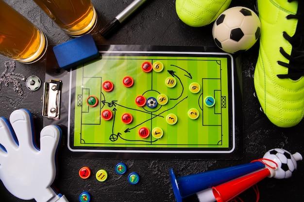 Due boccali di birra in schiuma, calcio balilla, palla, scarpe da calcio, pipa, sonaglio sul tavolo nero