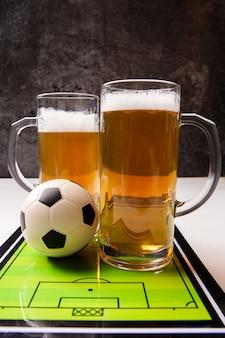 Due boccali di birra schiumosa, calcio balilla, palla sul tavolo bianco Foto Premium