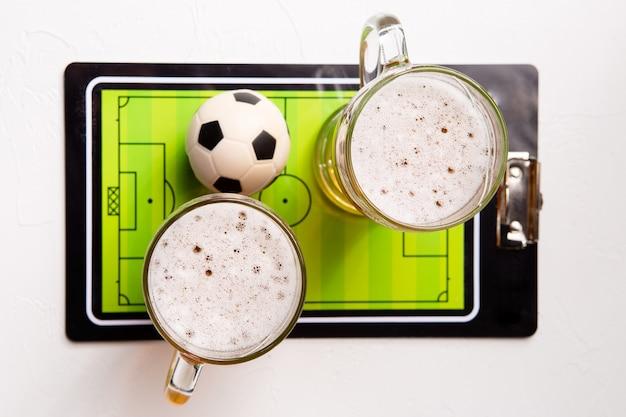 Due boccali di birra schiumosa, calcio balilla, palla sul tavolo bianco