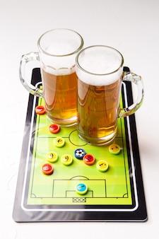 Due boccali di birra schiumosa con calcio balilla sul tavolo bianco