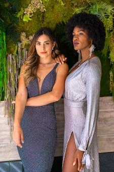 Due amici multietnici in abiti da ballo a una festa esclusiva. abiti da sera grigi e blu, ragazza bionda caucasica, ragazza nera con capelli afro