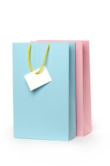 Due sacchetti di imballaggio multicolori con manici ed etichetta bianca isolati su sfondo bianco.