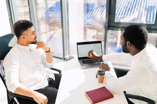 Due uomini d'affari multirazziali che guardano il grafico di crescita dell'azienda