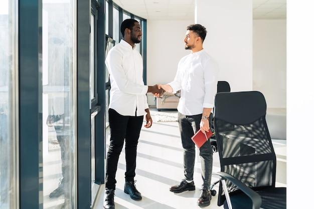 Due uomini d'affari multirazziali si stringono la mano