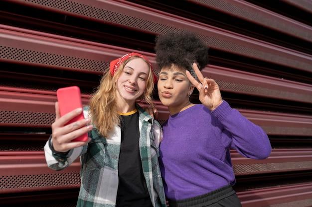 Due ragazze multirazziali che prendono selfie, due donne in città, donna afro e donna cauasiana