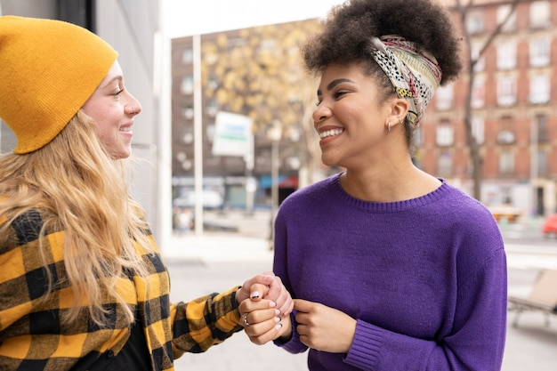 Due amiche multietniche multirazziali mano nella mano in giro per la città