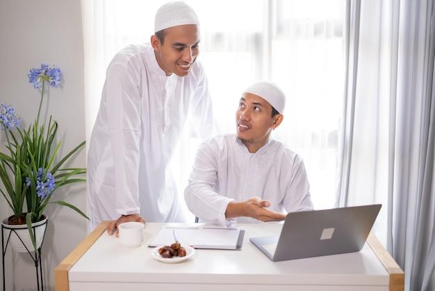 Due soci di affari musulmani che discutono e che incontrano insieme facendo uso del computer portatile