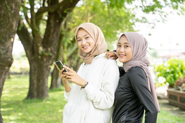 Due amici musulmani che usano lo smartphone dopo aver fatto esercizio all'aperto insieme