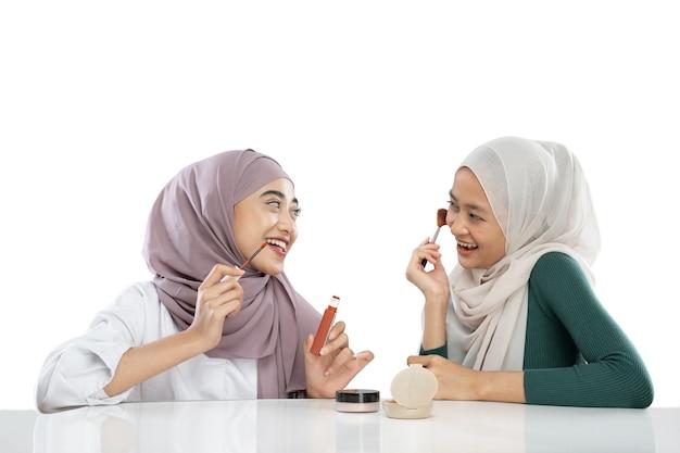 Due ragazze velate musulmane che usano il trucco usando il rossetto e una guancia con un pennello che fanno video