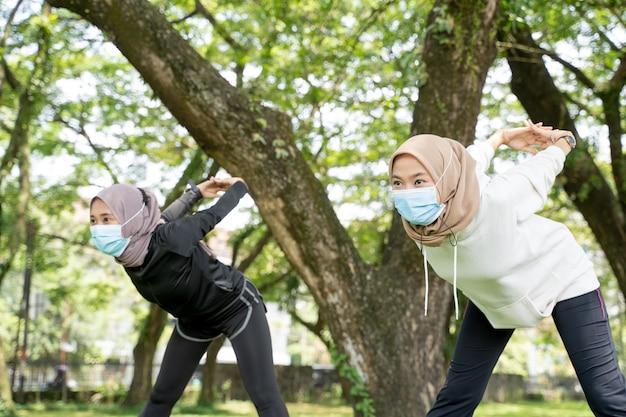 Due amiche musulmane si esercitano insieme e indossano una maschera per proteggersi dai virus