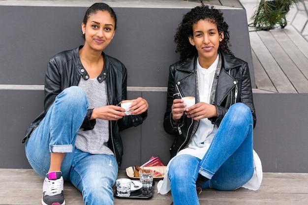Due amici adolescenti nordafricani che bevono insieme caffè fuori Foto Premium