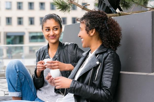 Due amici adolescenti nordafricani che bevono insieme caffè fuori