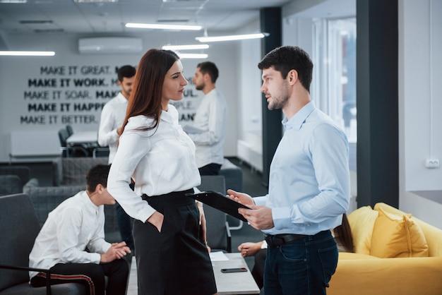 Due impiegati in abiti classici, parlando di fronte a dipendenti