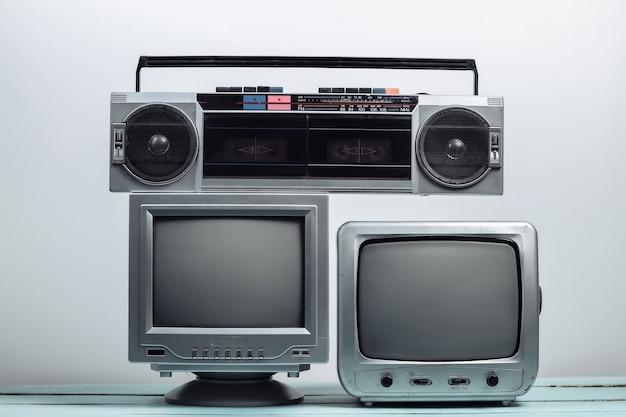 Due vecchi ricevitori tv con registratore a nastro audio su un muro bianco. media retrò