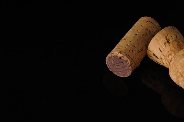 Due vecchi tappi per vino su sfondo nero con riflesso