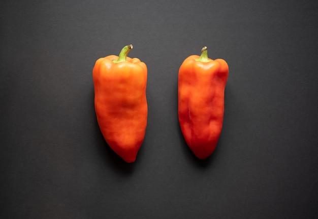 Due peperoni arancioni su uno sfondo nero vista dall'alto piatto lay