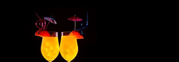 Due cocktail arancioni con ghiaccio su uno sfondo scuro, il concetto di rinfresco estivo