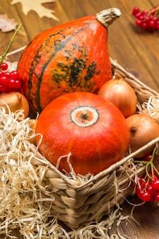 Due zucche e cipolle arancioni in cesto di vimini. paglia sul cestino. fondo in legno. vista dall'alto
