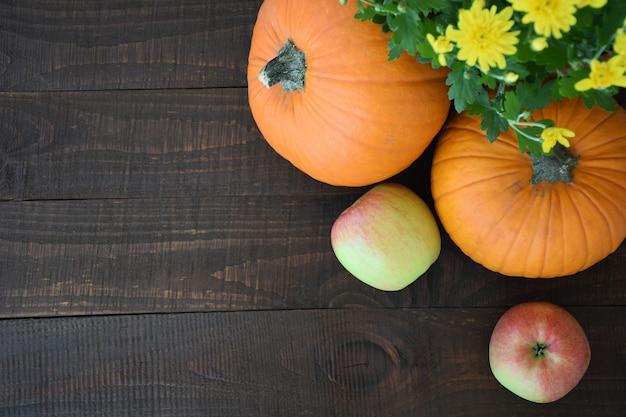 Due arancio e giallo crisantemi fiori zucche sullo sfondo della vecchia tavola di legno marrone.