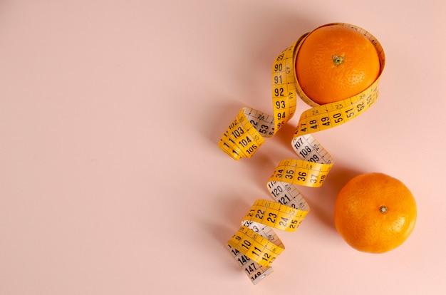 Due arance e nastro di misurazione sul rosa