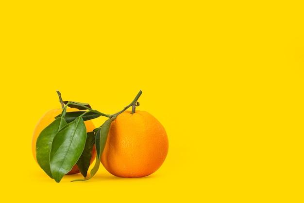 Due arance con foglie verdi su sfondo giallo
