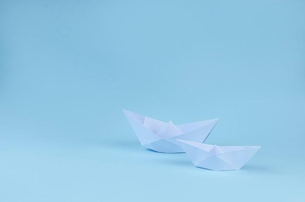 Due barche di carta origami sulla superficie azzurra