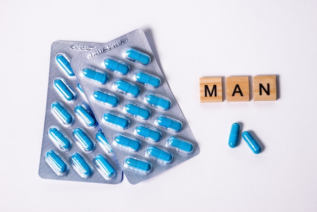 Due confezioni di capsule blu e scritta man. pillole per la salute degli uomini e l'energia sessuale su uno sfondo bianco isolato. concetto di erezione, potenza. trattamento di infertilità e impotenza maschili.