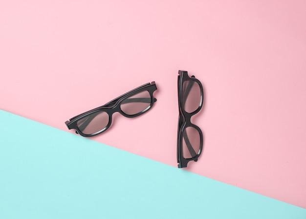 Due paia di occhiali 3d su una superficie pastello blu rosa. vista dall'alto. minimalismo
