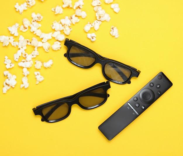 Occhiali 3d a due paia, telecomando tv, popcorn su giallo. vista dall'alto, piatto