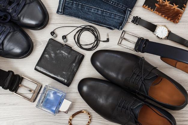 Due paia di scarpe da uomo in pelle nera, cinture da uomo, jeans, acqua di colonia da uomo, orologio da polso, cuffie.