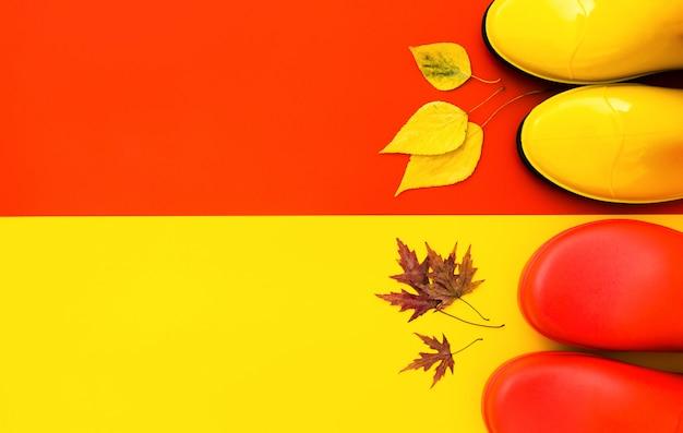 Due paia di stivali di gomma lucenti: rosso e giallo sono su uno sfondo contrastante e davanti a loro ci sono le foglie d'autunno