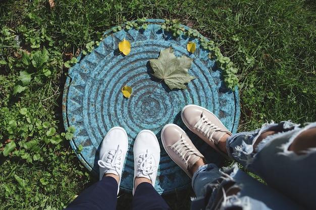 Due paia di gambe di donne e foglie cadute sul tombino