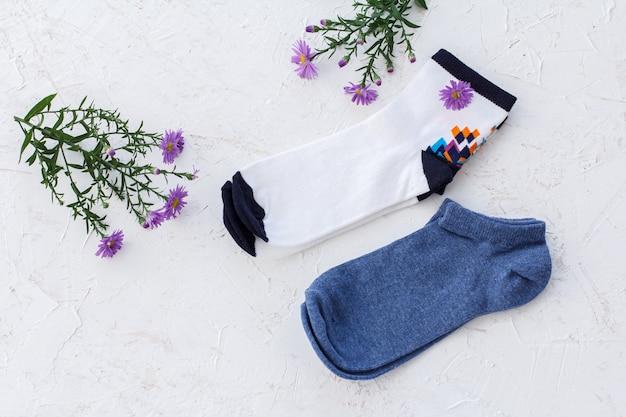 Due paia di calze da donna e fiori su fondo bianco strutturato, vista dall'alto.