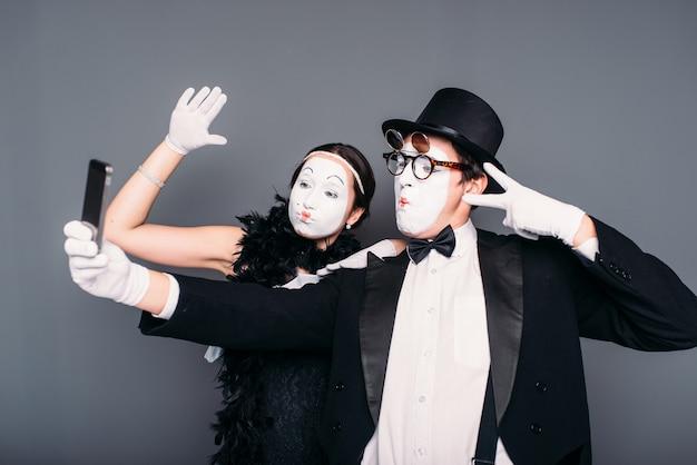 Due interpreti di teatro pantomima fanno selfie sulla fotocamera.