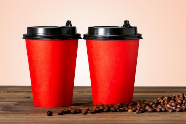 Due bicchieri di carta di caffè e chicchi di caffè sulla tavola di legno.