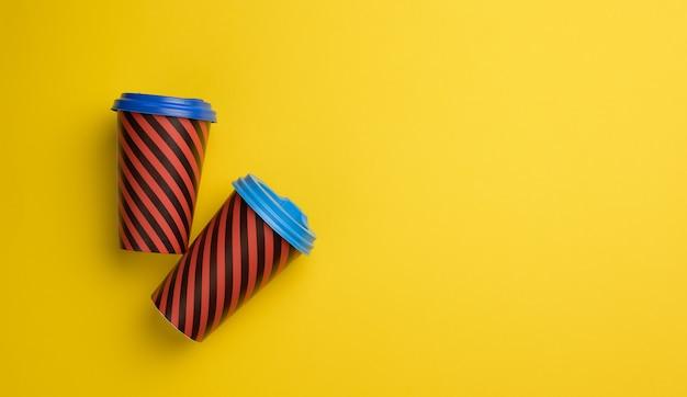 Due bicchieri di carta rossa con coperchio in plastica su sfondo giallo, vista dall'alto, spazio copia