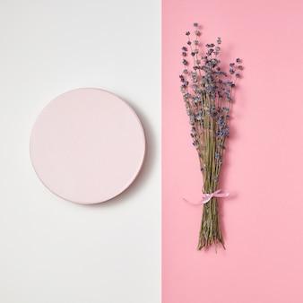 Due parti della scheda creativa con cornice rotonda e mazzo eco naturale di fiori di lavanda su una parete grigio chiaro e rosa a due tonalità, copia dello spazio.
