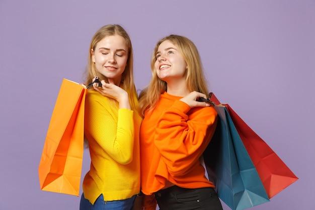 Due giovani sorelle gemelle bionde pensierose in abiti vivaci che tengono la borsa del pacchetto con gli acquisti dopo lo shopping isolato sulla parete blu viola. concetto di stile di vita familiare di persone. .