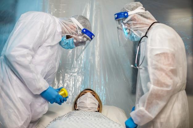 Due persone si prendono cura di una donna con un virus sdraiata su un divano in un ospedale da campo. virus corona pandemico