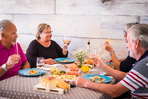 Due coppie di persone mangiano insieme a casa durante il giorno. insieme attività per il tempo libero al coperto per adulti uomini e donne adulti con i capelli bianchi. sorridi e divertiti in amicizia