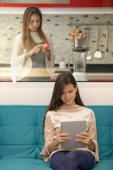 Due persone, figlia che gioca e guarda lo smartphone mentre la madre cucina il cibo per lei, concetto di problema nella vita moderna della famiglia e dell'adolescente